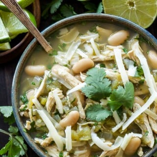 White Chicken Chili in bowl with a spoon topped with cheese and cilantro. Cut limes in the background.