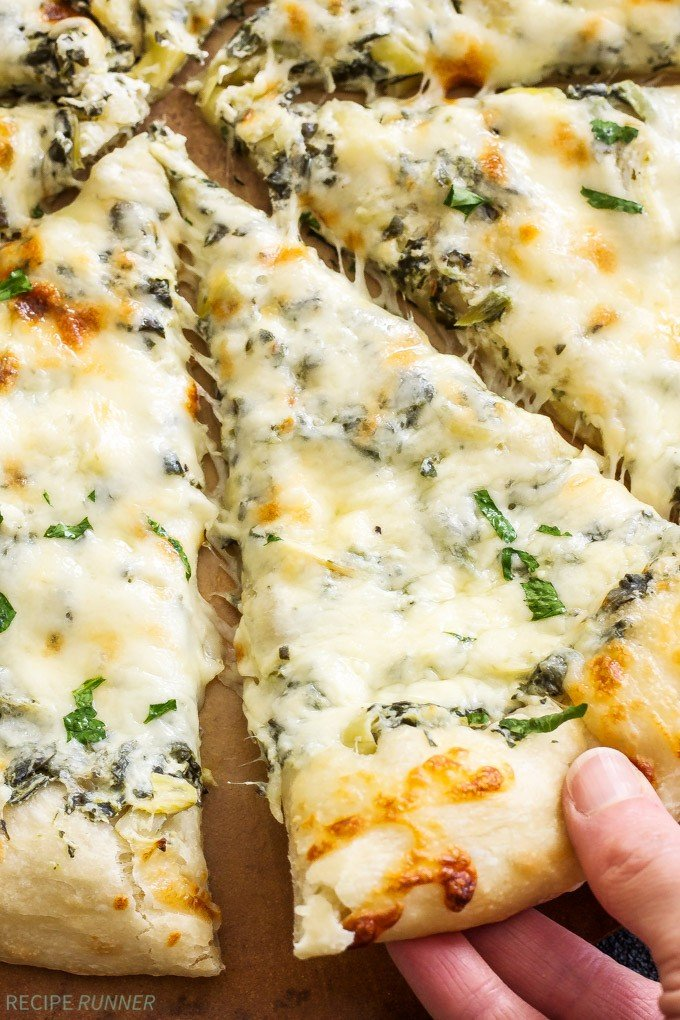 Spinach and Artichoke Dip Pizza on a pizza stone with a hand pulling a slice out of the pizza.
