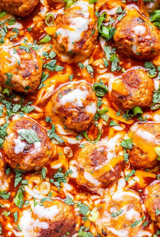 closeup photo of Skillet Enchilada Meatballs covered in melted cheese.