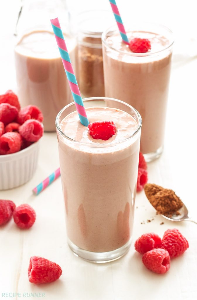 Two chocolate raspberry smothies in glasses with blue and pink striped straws. Raspberries are scattered around the smoothies.