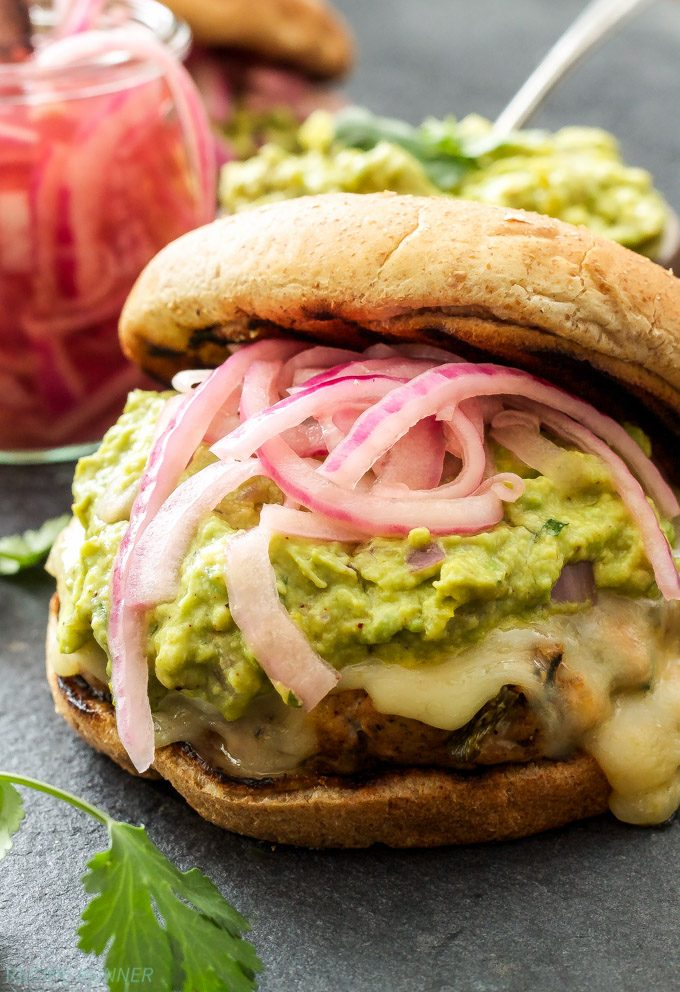 Green Chile Turkey Burger on a bun topped with cheese, Guacamole and Pickled Red Onions.
