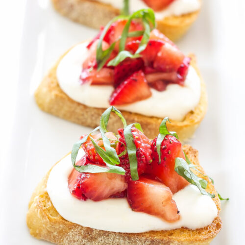Strawberry Balsamic Crostini with Whipped Ricotta on a white plate.