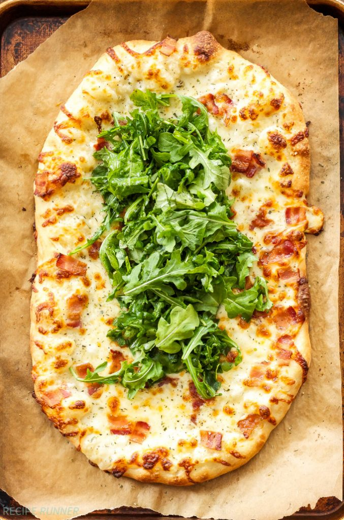 White Pizza with Bacon and Arugula on parchment paper