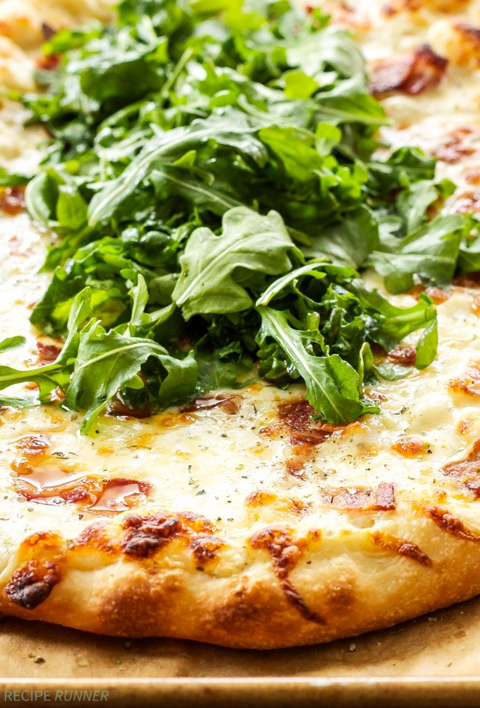 White Pizza with Bacon and Arugula | Topped with a parmesan cream sauce, smoked mozzarella, bacon and a fresh arugula salad, it's sure to become your favorite white pizza!