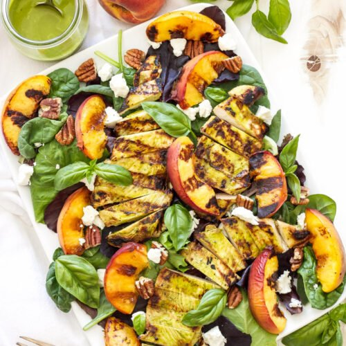 Grilled Chicken, Peach, Pecan, and Goat Cheese Salad with Basil Vinaigrette on white serving plate and a glass jar with the vinaigrette and spoon on the side.