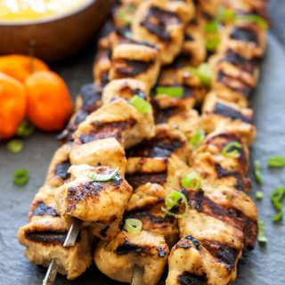 Jerk Chicken Skewers with Mango Habanero Sauce on gray stone platter with sauce in wooden bowl