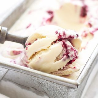 berry cheesecake ice cream in a loaf pan with an ice cream scoop scooping some out.