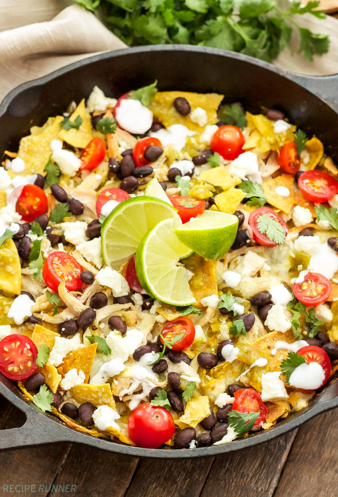 Skillet Green Chile Chicken Chilaquiles | Corn tortilla chips tossed in a green chile sauce and piled high with chicken, black beans, cheese and all of your favorite Mexican toppings!