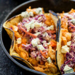 Buffalo Chicken Tacos with Blue Cheese Coleslaw | Shredded chicken coated in buffalo sauce and topped with a creamy blue cheese coleslaw. These slow cooker tacos are perfect for a weeknight dinner or game day!