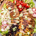 Southwest Chicken Salad with Avocado Lime Dressing on a wooden platter.