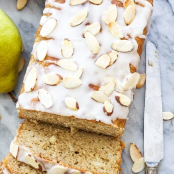 Overhead photo of a loaf of cardamom pear quick bread with several slices cut from it. White almond glaze on top with sliced almonds.