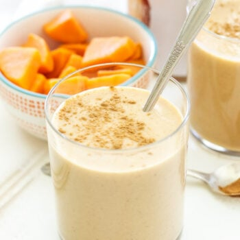 Cinnamon Sweet Potato Almond Butter Smoothie in a glass with a spoon sprinkled with cinnamon on top.