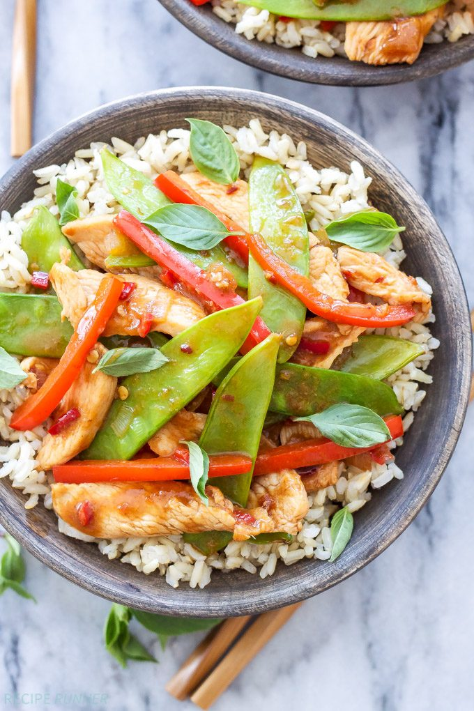 Thai chicken stir fry on top of rice in a gray bowl.