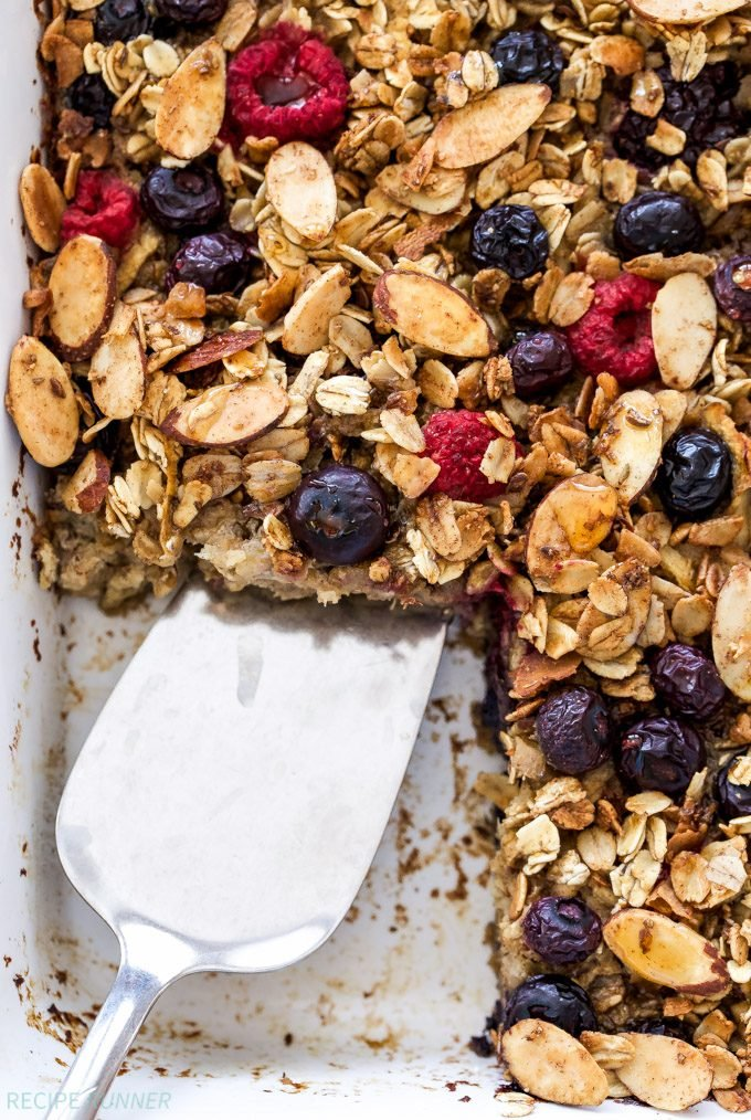 Cinnamon Apple Berry Baked Oatmeal in white baking dish with square cut out. Oatmeal topped with blueberries, raspberries and sliced almonds.