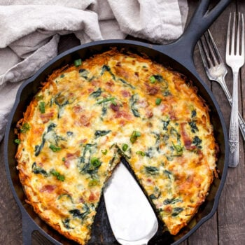 Spinach Bacon, Cheese Quiche with Sweet Potato Crust in a cast iron skillet with a piece cut out and a serving spatula in it's place.