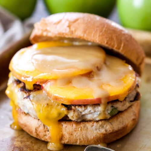 Turkey burger on a bun topped with cheddar cheese, apple slices and honey mustard sauce.