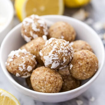Lemon Coconut Cashew Energy Bites in a white bowl with lemons behind the bowl.