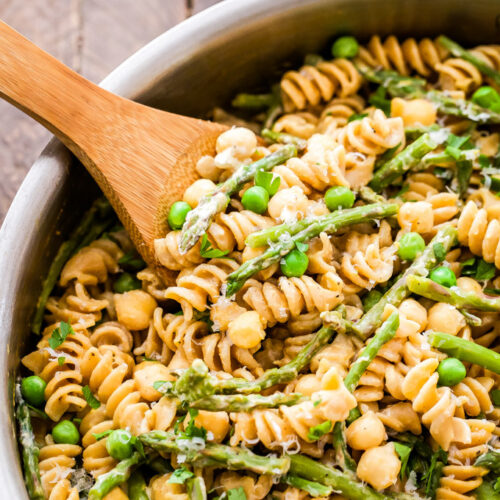 Creamy Lemon Goat Cheese Pasta with Chickpeas and Asparagus in silver pan with wooden spoon.