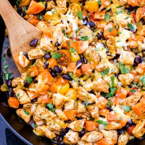 Mexican Chicken, Sweet Potatoes and Black Beans topped with melted cheese in a cast iron Skillet with a wooden serving spoon in the skillet.