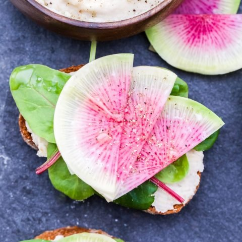 White Bean Crostini with Watermelon Radishes on slate serving stone and a small wooden bowl filled with the white bean purée