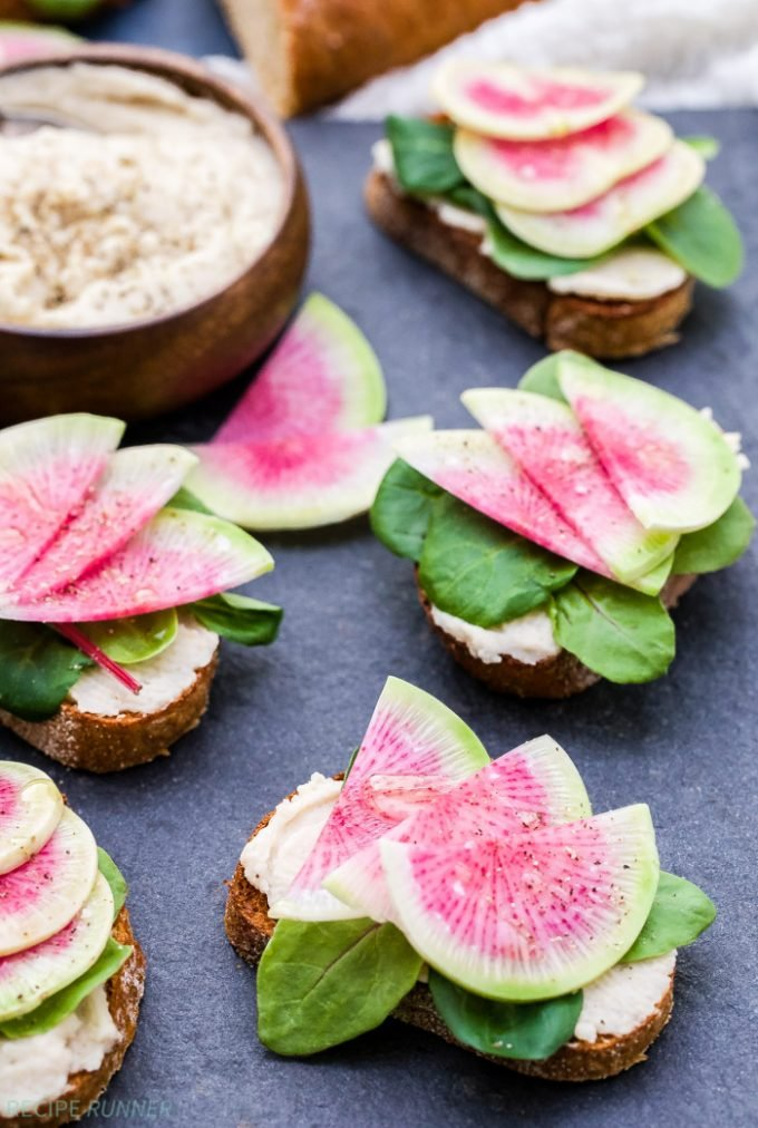 White Bean Crostini with Watermelon Radishes are the perfect spring bite! Toasted baguette topped with creamy white bean spread, spring greens and crunchy watermelon radishes is an easy appetizer to go with dinner or savory bite to have with brunch.