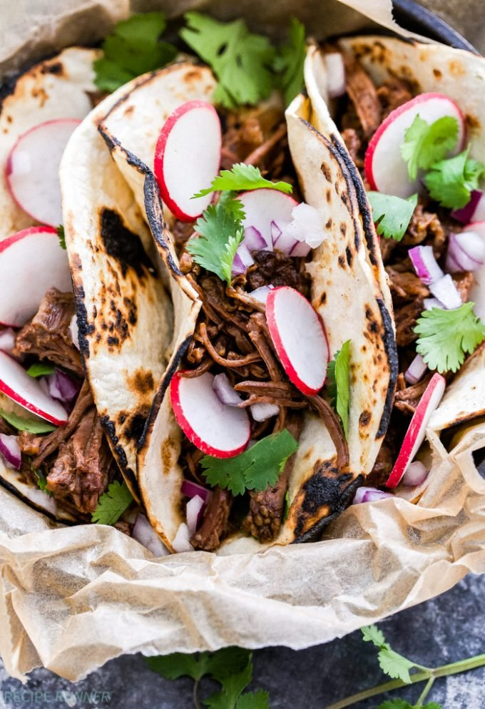 Sweet and Spicy Ancho Chile Short Rib Tacos topped with radishes and cilantro.