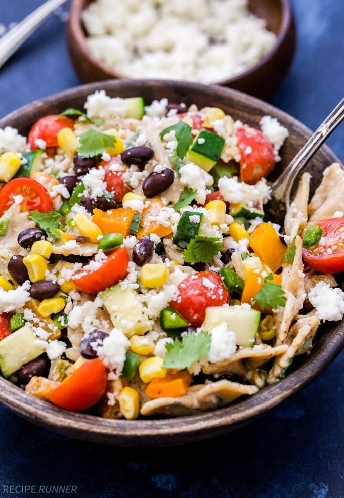 Southwest Vegetarian Pasta Salad with tomatoes, black beans, corn in a wooden bowl with spoon.