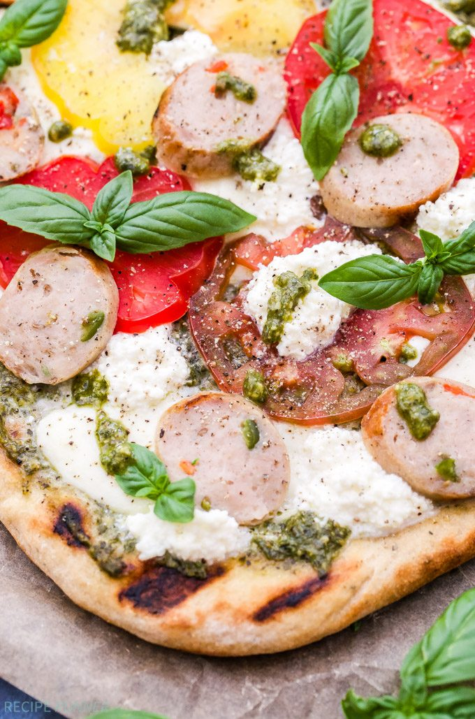 Keep the heat out of the kitchen and try grilling your next pizza! This Grilled Tomato, Basil, Pesto Pizza with Chicken Sausage, Mozzarella and Ricotta not only tastes amazing, but it's easy to make! Perfect for dinner or an appetizer for your next party.