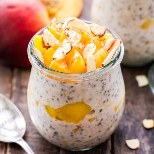 Cinnamon Honey Peach Overnight Oats topped with chopped peaches and sliced almonds in a jar with a spoon next to the jar.