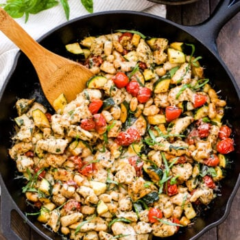 Cast iron skillet with Italian seasoned chicken and vegetables with a wooden spoon in the skillet.