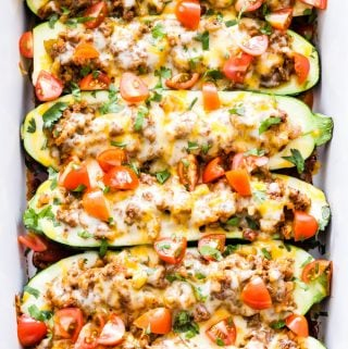Cheesy Taco Stuffed Zucchini Boats are a great way to enjoy a low-carb taco night and get an extra serving of vegetables! Packed with a flavorful taco filling and topped with melted cheese, you won't miss the tortilla!
