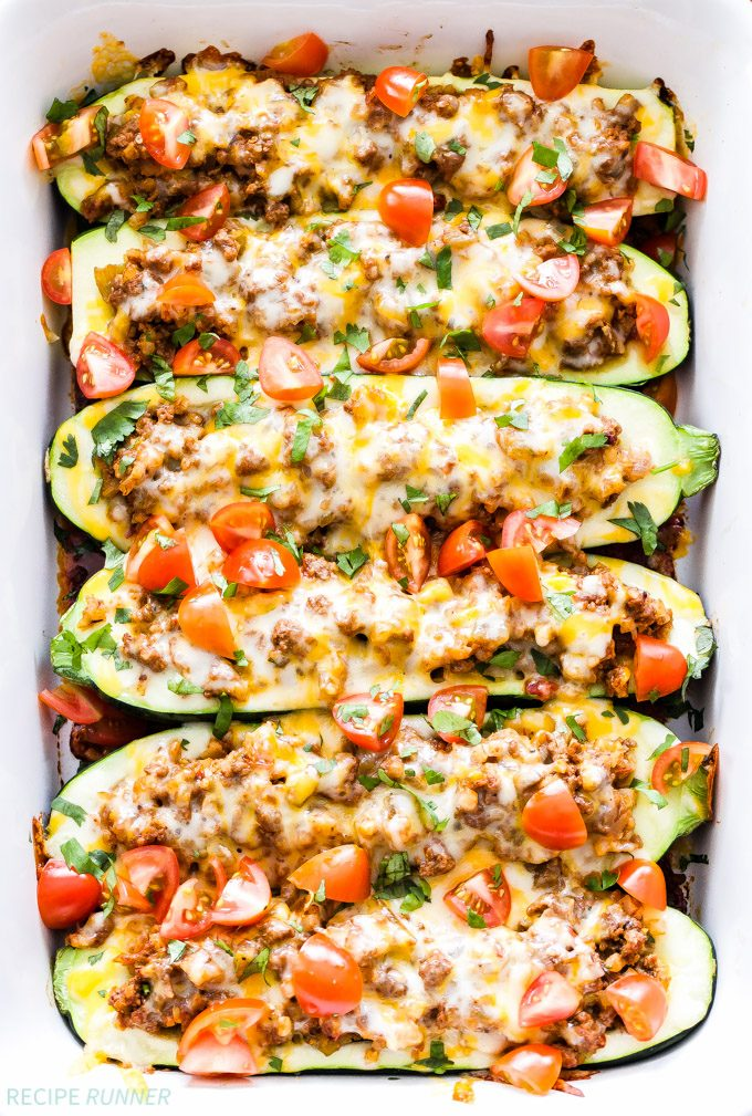 Overhead photo of six Taco Stuffed Zucchini Boats filled with ground beef and topped with melted cheese, tomatoes and cilantro.