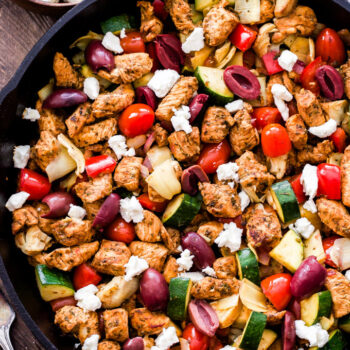 Greek Chicken and Vegetables in a black cast iron skillet with a bowl of feta behind it. Skillet includes chicken, zucchini, tomatoes, kalamata olives and feta crumbles.