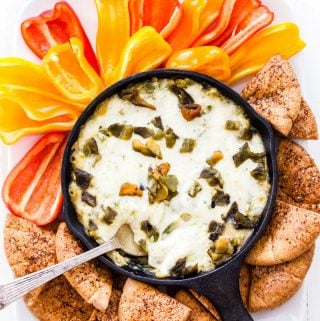 Looking for a healthier version of spinach artichoke dip? Look no further than this Baked Green Chile Spinach Artichoke Hummus Dip! All the classic flavors combined with green chiles, creamy hummus and plenty of melted cheese. This dip will be a total crowd pleaser at your next party!