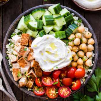 These Healthy Chicken Shawarma Bowls need to be in your weeknight dinner rotation! Fresh vegetables, chickpeas, seasoned chicken and the most amazing spiced yogurt sauce. Keep it low-carb with cauliflower rice or substitute with your favorite whole grain for a complete balanced meal!