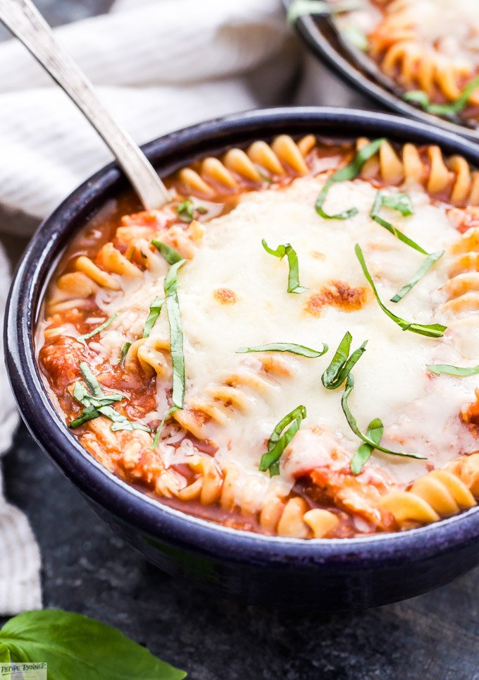 Everything you love about chicken parmesan in a warm bowl of soup! You'll love this easy and comforting Slow Cooker Chicken Parmesan Soup. It's sure to be a family favorite! #soup #glutenfree