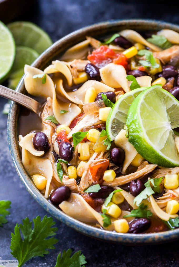 Classic chicken noodle soup gets a kick of Southwest flavor! Full of chicken, green chiles, black beans, corn and flavorful spices. You'll love this hearty and easy to make Slow Cooker Southwest Chicken Noodle Soup.