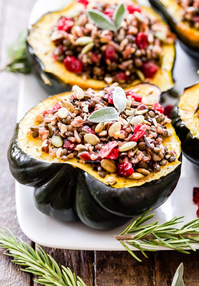 These Lentil, Wild Rice and Cranberry Stuffed Squash will not only be a beautiful and flavorful side dish for your Thanksgiving table, but they're hearty enough to be a main dish for your vegetarian or vegan guests. #lentils #acornsquash #thanksgiving #vegan #vegetarian #glutenfree #rice #cranberries