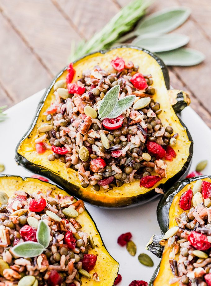 These Lentil, Wild Rice and Cranberry Stuffed Squash will not only be a beautiful and flavorful side dish for your Thanksgiving table, but they're hearty enough to be a main dish for your vegetarian or vegan guests.#lentils #acornsquash #thanksgiving #vegan #vegetarian #glutenfree #rice #cranberries