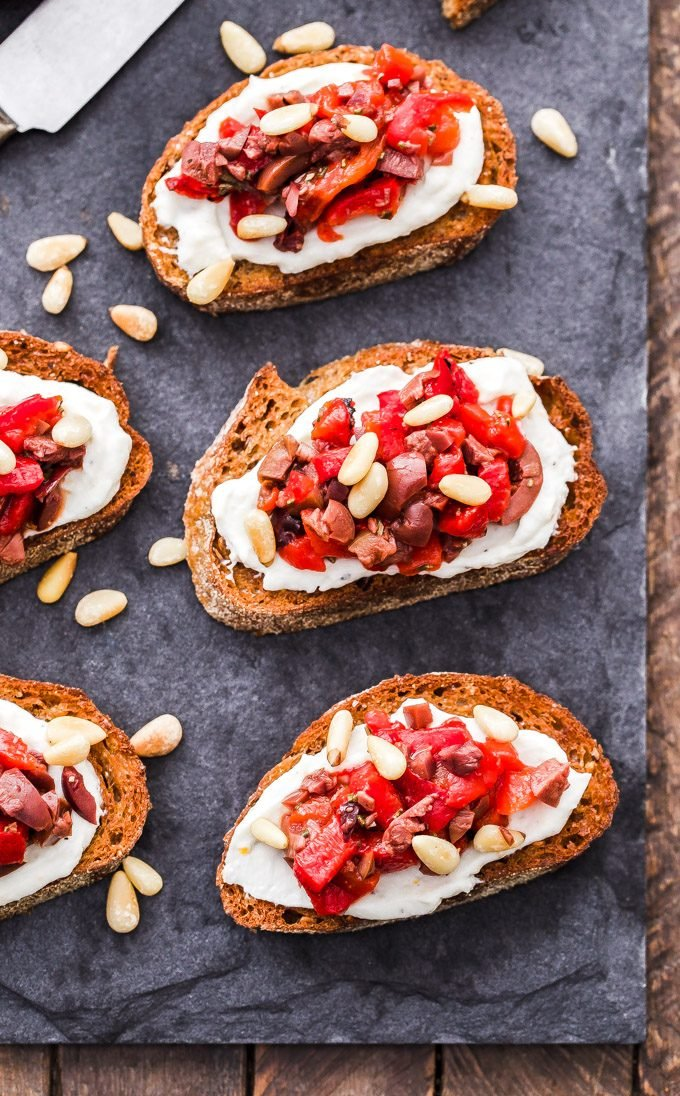 Every party needs a crostini and these Roasted Red Pepper, Olive and Ricotta Crostini deliver major flavor! briny olives, sweet roasted red peppers and creamy ricotta are a perfect pairing in these little bites.