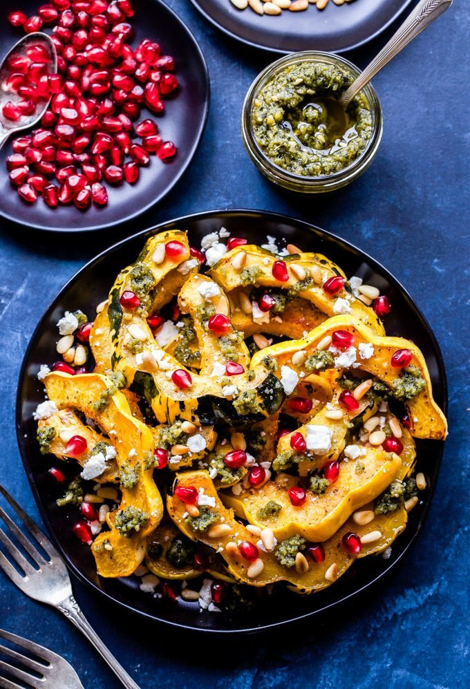 Perfectly roasted squash topped with savory, salty and sweet toppings! This Roasted Squash with Pesto, Feta and Pomegranate Seeds is loaded with flavor and the perfect side dish to make this winter! #squash #healthyrecipe #feta #pesto #pomegranate #glutenfree #vegetarian #easyrecipe