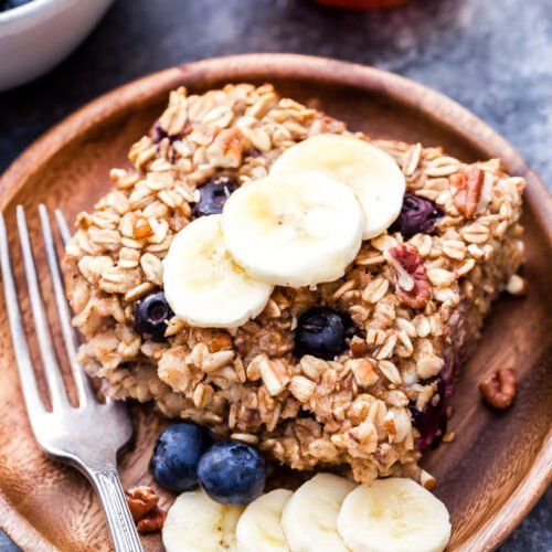Blueberry Banana Bread Baked Oatmeal slice on wooden plate with fork and banana slices and blueberries for garnish.