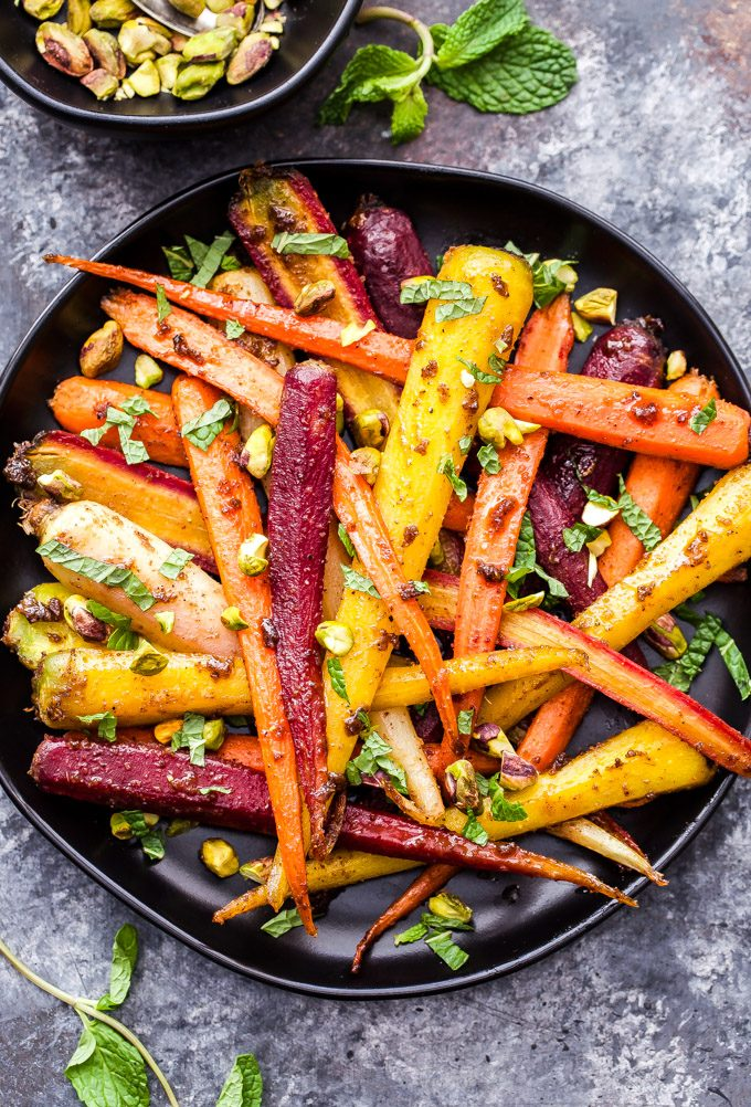 Garam Masala and Honey Roasted Carrots on black plate with pistachios