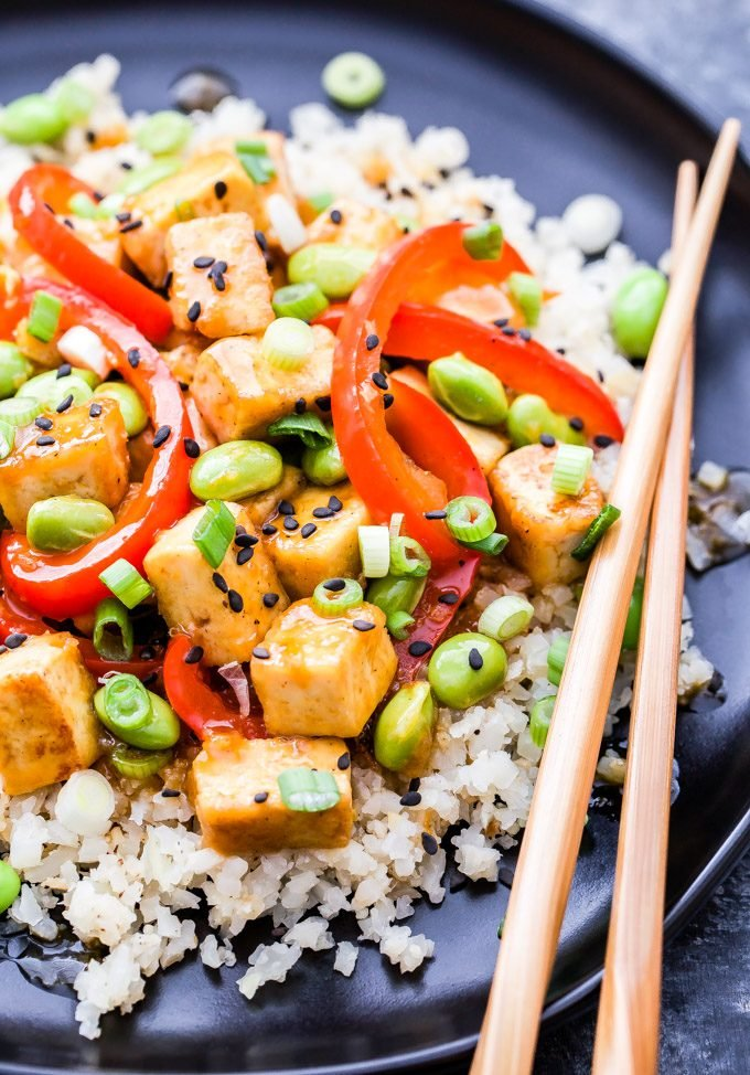 Orange Tofu and Edamame Stir-Fry is perfect for an easy, meatless dinner. Crisp tofu, sweet red bell peppers and protein packed edamame are coated in a fresh and flavorful orange sauce. You'll love this healthy, one pan dinner!  #tofu #orange #edamame #stirfry #takeout #healthyrecipe #dinner #glutenfree #vegetarian