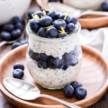Blueberry Lemon Overnight Oats in a glass jar on top of a wooden plate with a spoon on the plate. Oats are topped with fresh blueberries and lemon zest.