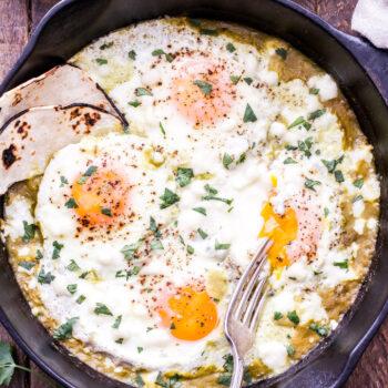 Salsa verde baked eggs in black cast iron skillet