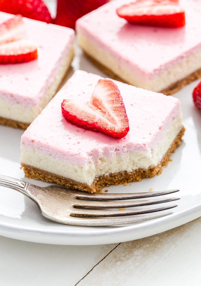 Strawberry greek yogurt cheesecake bar with a piece cut off and a fork in front of it.