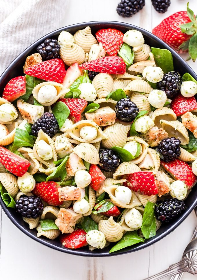 Chicken and Berry Pesto Pasta Salad in black bowl with berries on the side