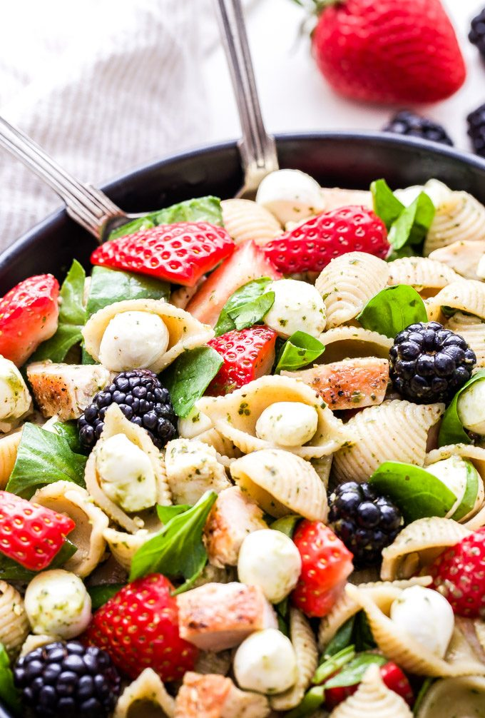 This Chicken and Berry Pesto Pasta Salad is a flavorful and easy to make main dish salad. All the flavors of caprese salad, but using berries instead of tomatoes! It's perfect for spring and summer! #pastasalad #strawberries #pesto #chicken #salad
