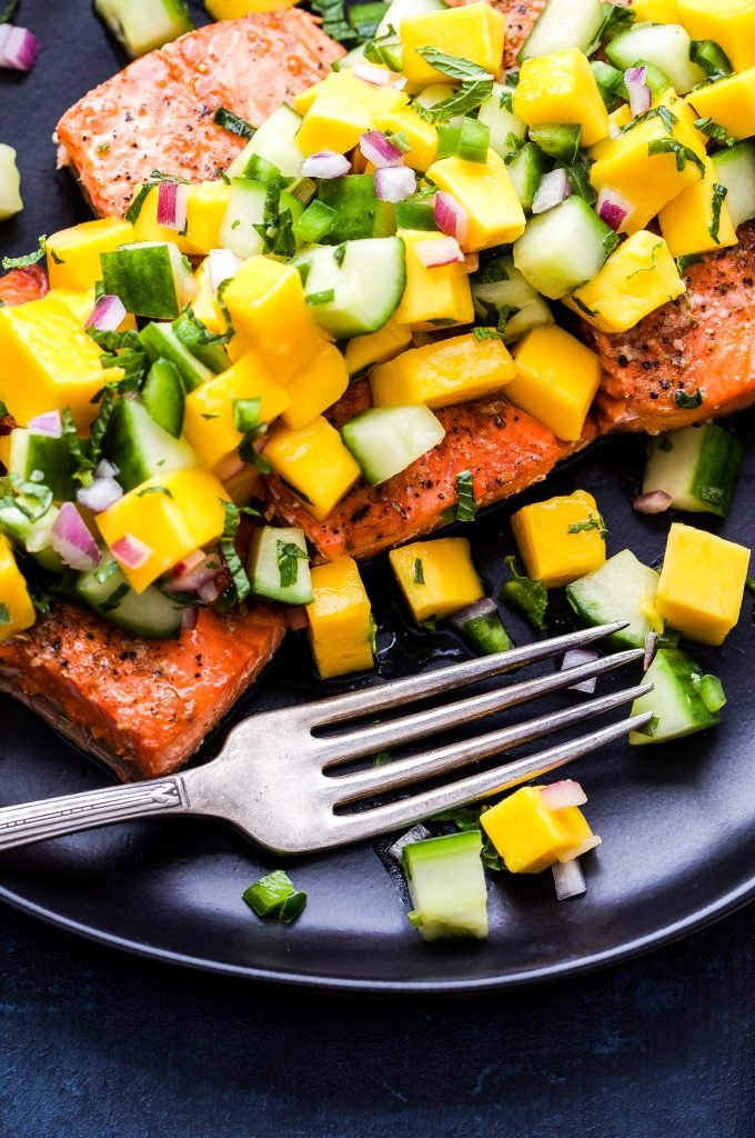 Grilled Salmon with Mango Cucumber Mint Salsa on black plate with fork